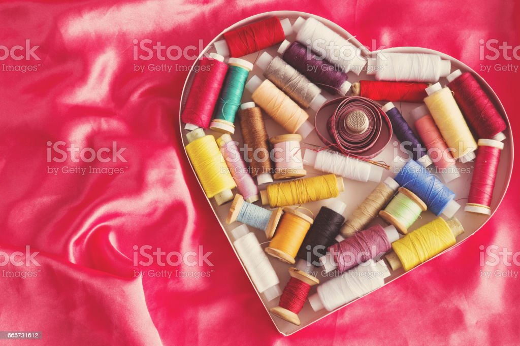 Colorful threads, needle, and other accessories in heart form box on the silk background. Loving a sewing works. Womanly hobby. Handmade. stock photo
