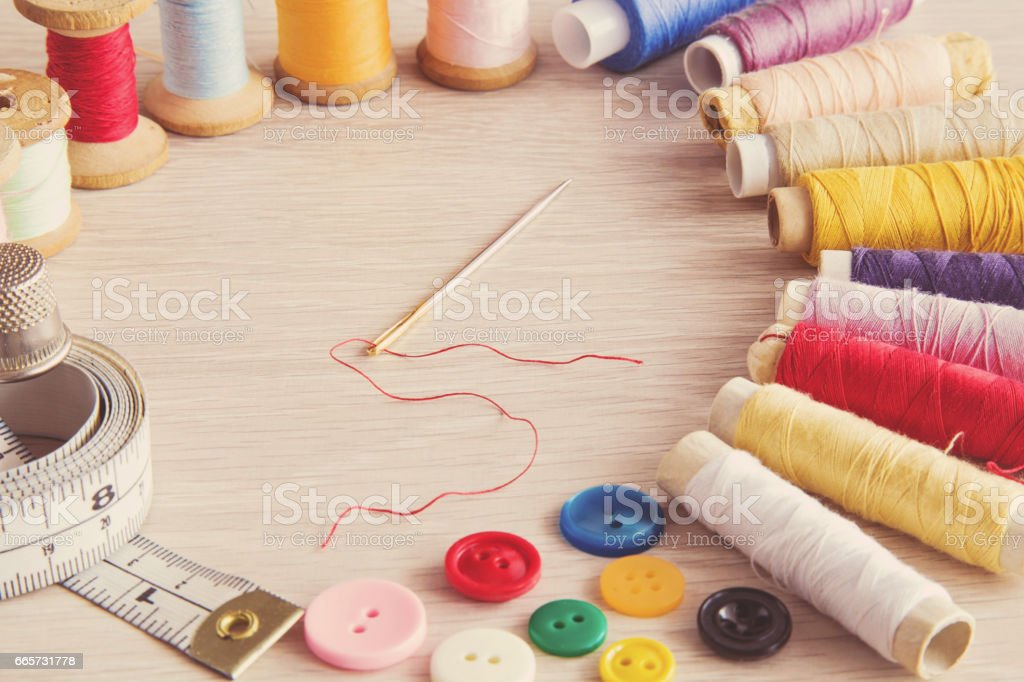 Colorful threads, needle and other accessories on the wooden table. Sewing works. Handmade. Womanly hobby. stock photo