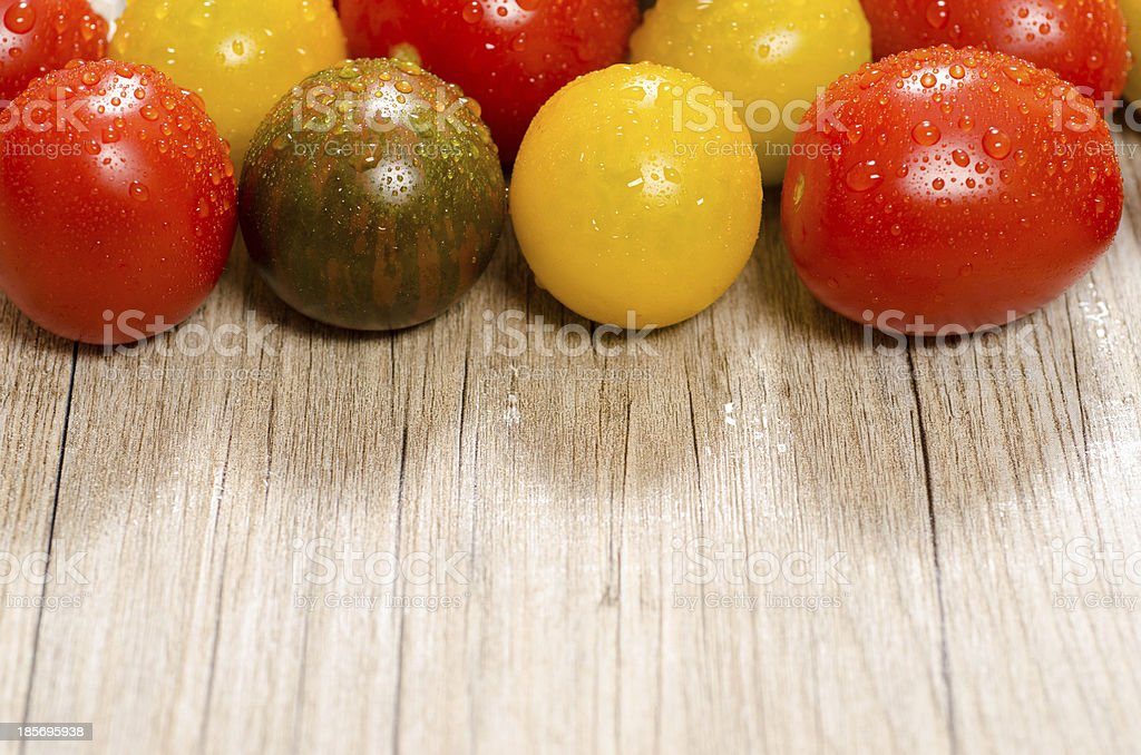 Colorful tomatoes on a wooden board  with text space royalty-free stock photo