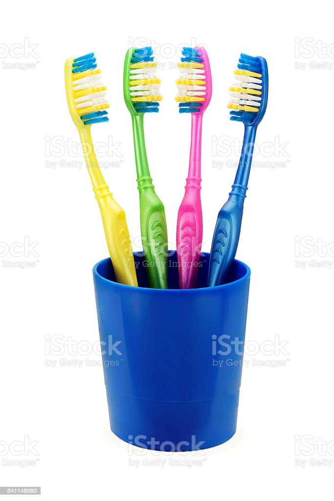 colorful toothbrushes in blue cup stock photo