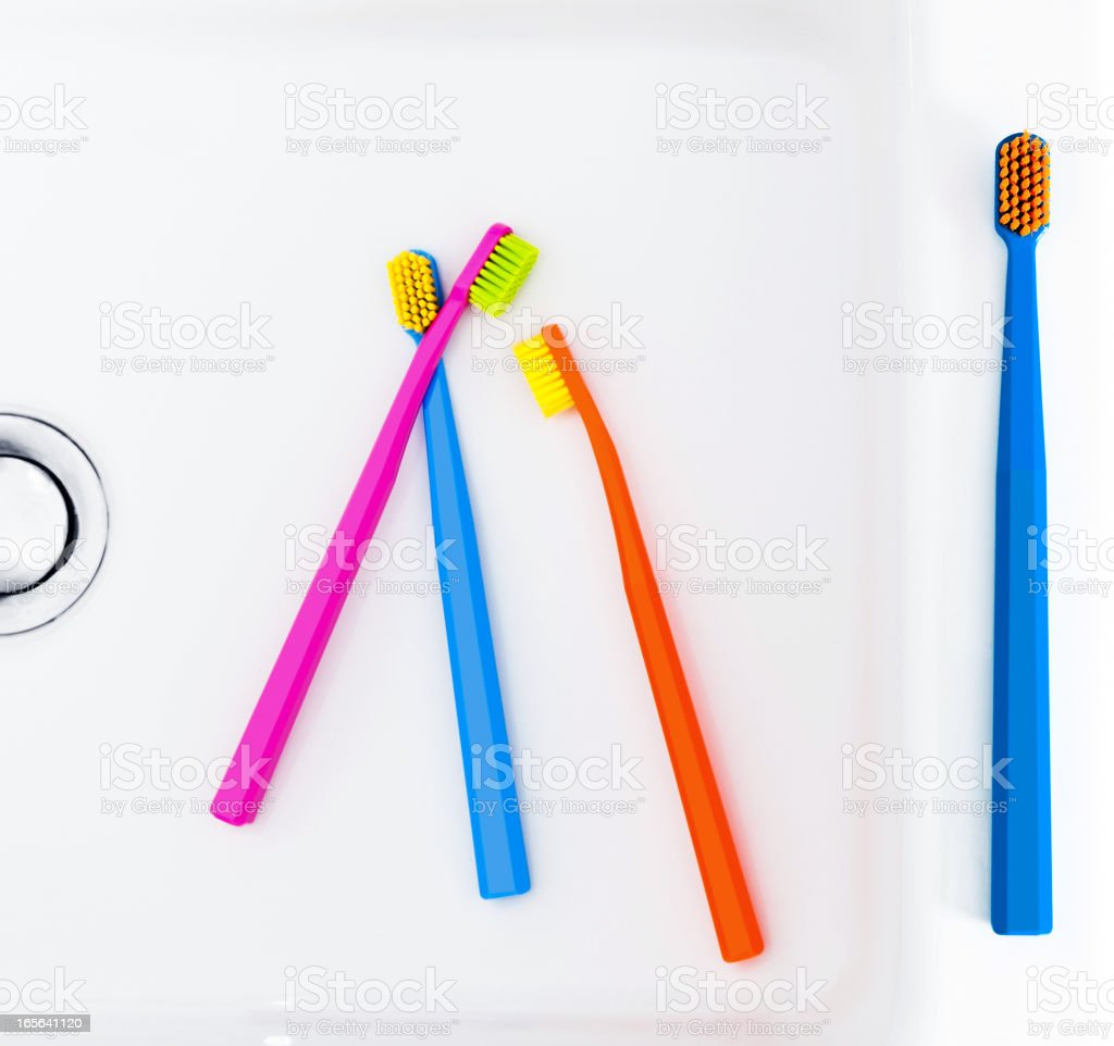 Colorful toothbrushes in sink stock photo