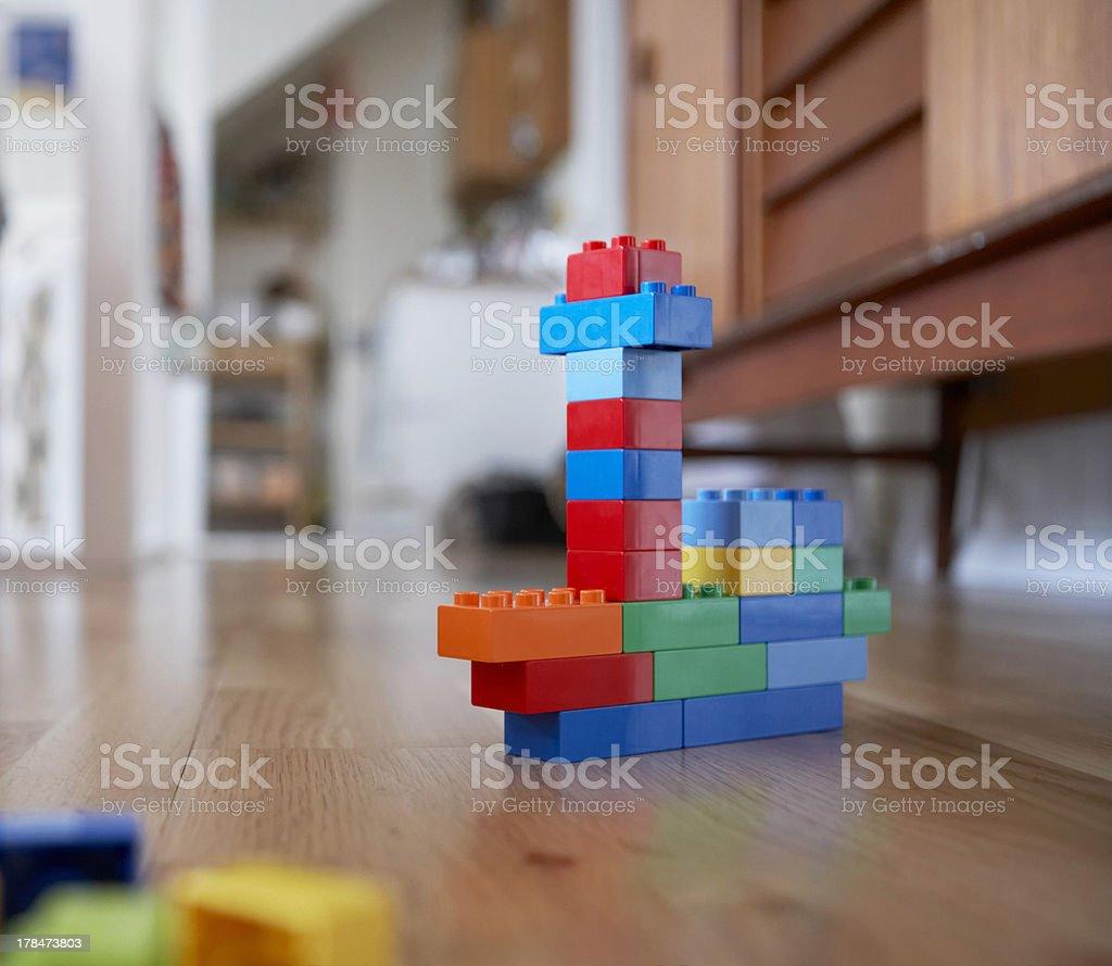 Colorful toy blocks on living room hardwood floor stock photo