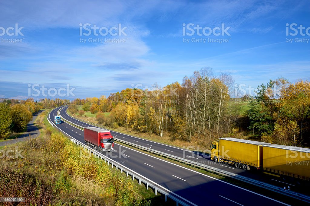 Colorful trucks driving on the asphalt highway in autumn landscape stock photo