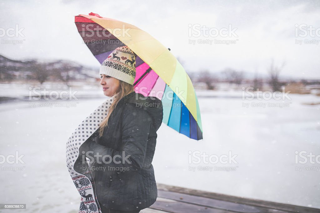 Colorful umbrella in winter nature holding by young girl stock photo