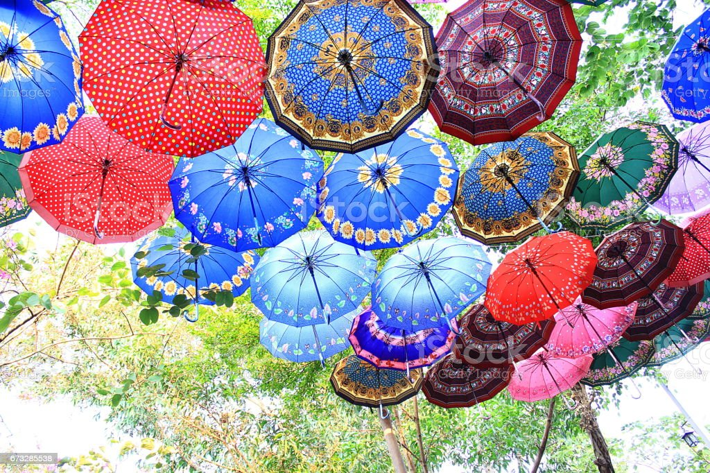 Colorful umbrellas are hanging outdoor under tree branches stock photo
