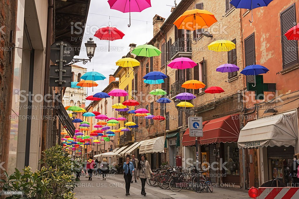 Colorful umbrellas hanging above street of Ferrara, Italy stock photo