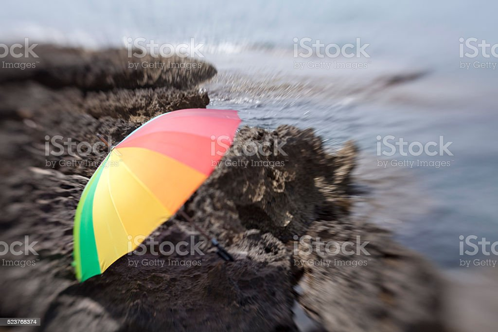 colorful umbrella,sea and rock with lensbabies stock photo