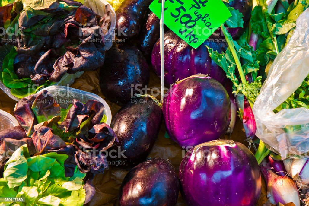 Colorful vegetables from organic agriculture exhibited in a italian market with 'naubergines on foreground stock photo