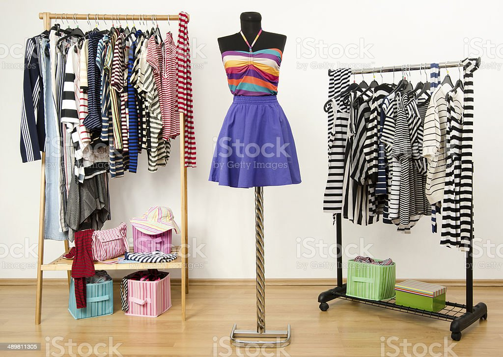 Colorful wardrobe full of clothes and accessories with stripes pattern. stock photo