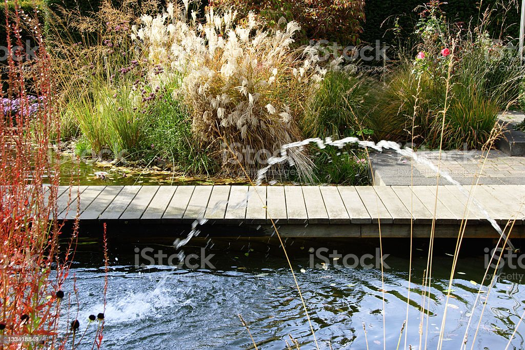 Colorful water garden with fountain and dock stock photo