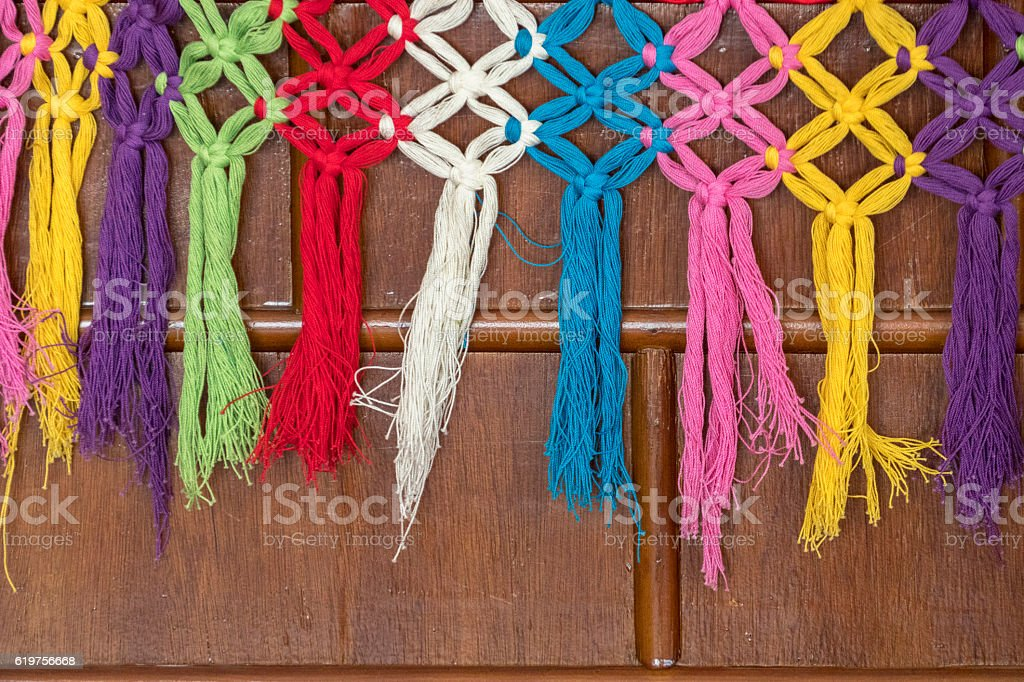 colorful weaved tassel covered on wooden furniture stock photo