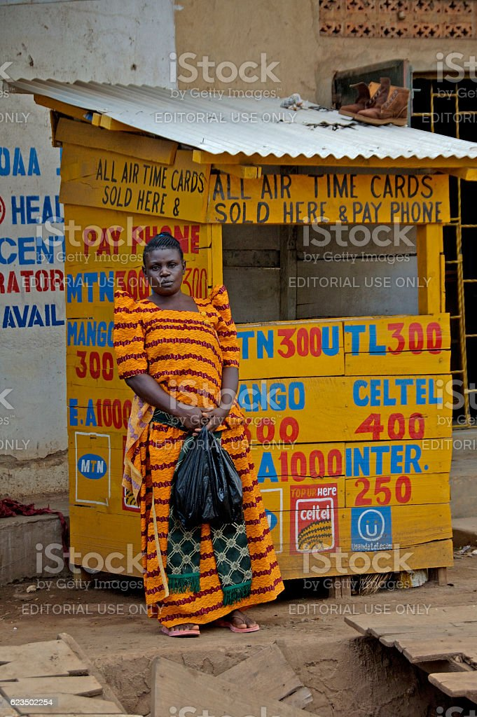 Colorful woman in front of her shop. stock photo