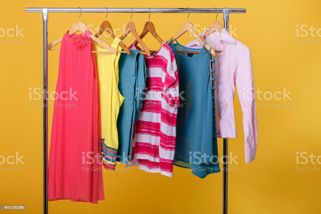 colorful womens clothes on hangers on rack on orange background. stock photo
