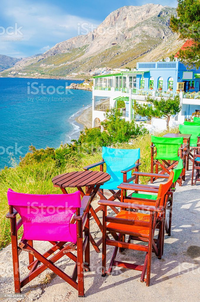 Colorful wooden chairs with view on sea, Greece stock photo