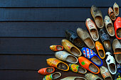 Colorful wooden clogs on dark wooden panels