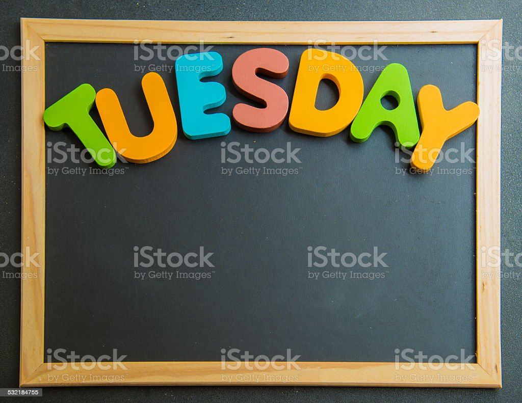 Colorful wooden word Tuesday on black board stock photo
