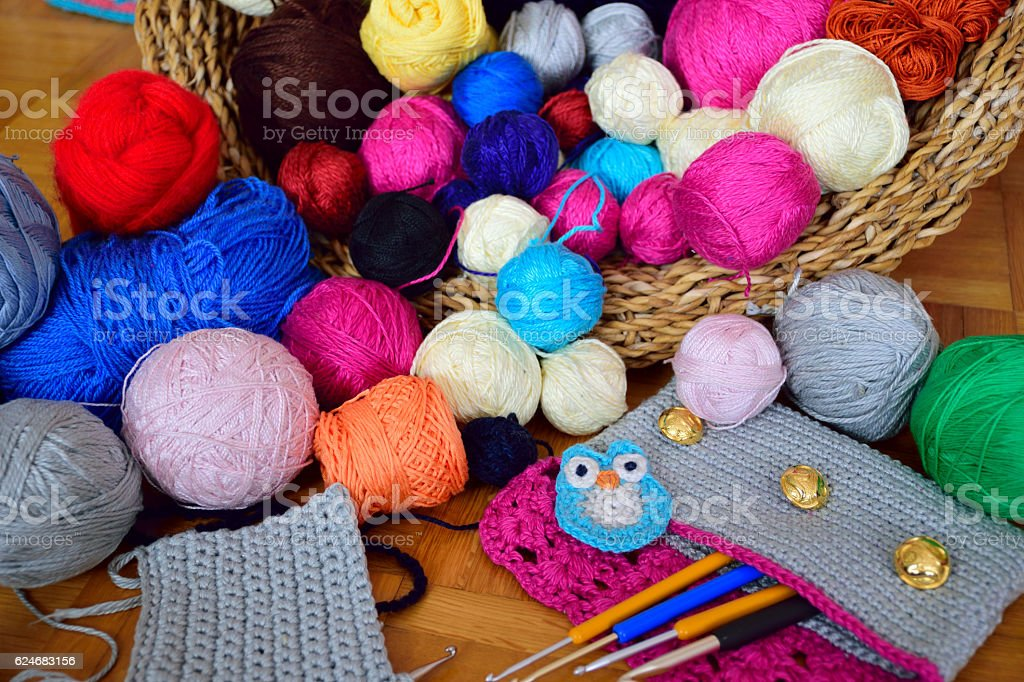 Colorful yarn balls in a basket, with crochet supplies stock photo