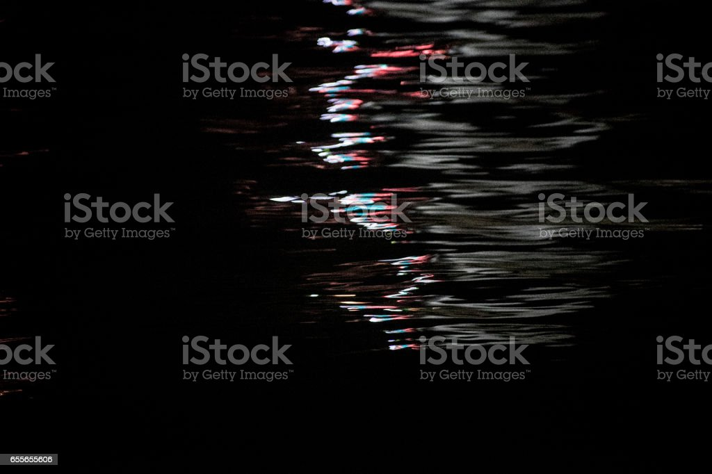 colorfull light reflections at sea in the night stock photo