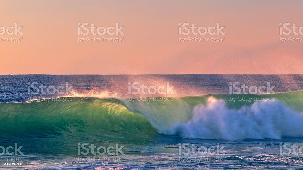 Colorfull wave crashing at sunset stock photo