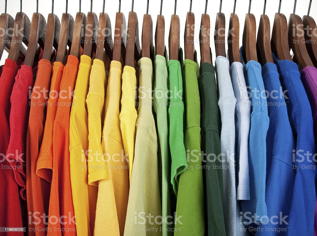 Colors of rainbow, clothes on wooden hangers stock photo