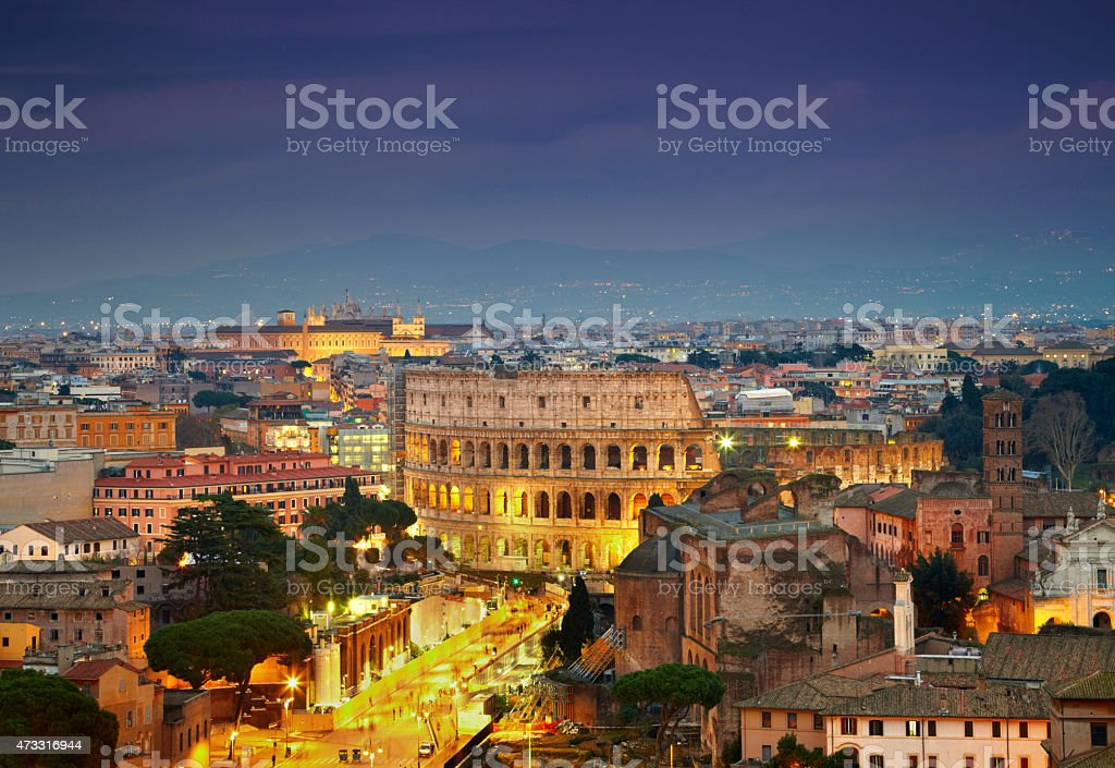 Colosseum in Rome after sunse with citylights stock photo