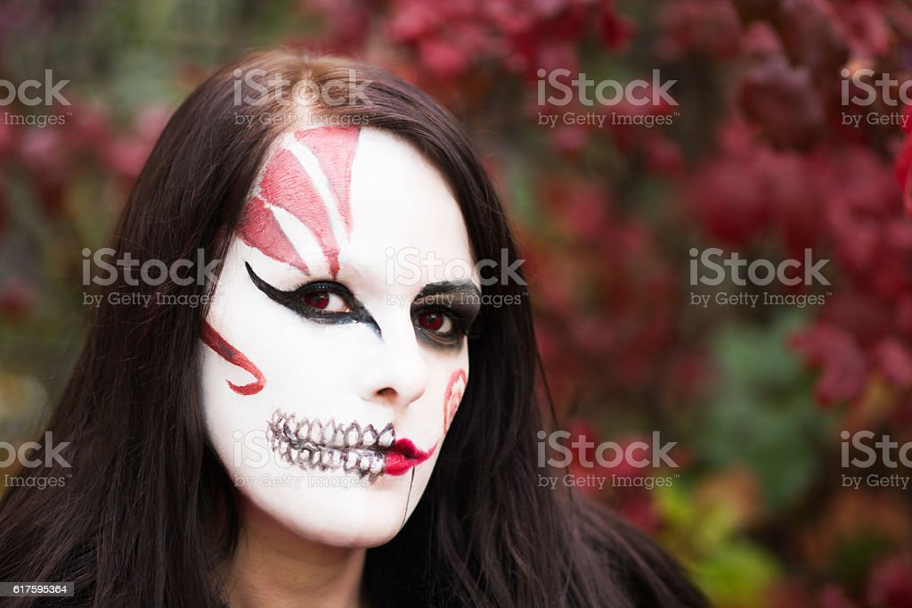 Colour image of woman wearing Halloween makeup in autumn garden. stock photo