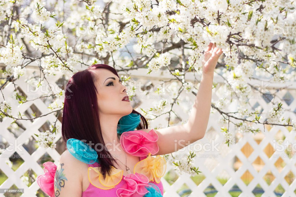 Colour image of young woman in Spring garden looking up. stock photo