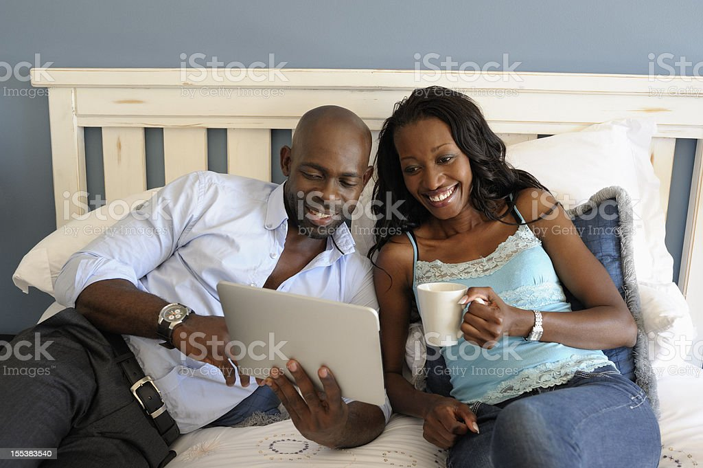 Coloured Couple Looking at Tablet Computer stock photo