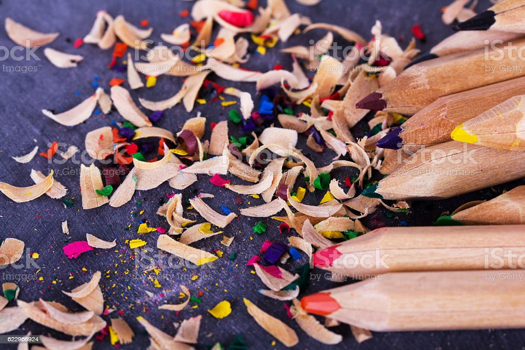 Coloured pencils and shavings against a black background stock photo