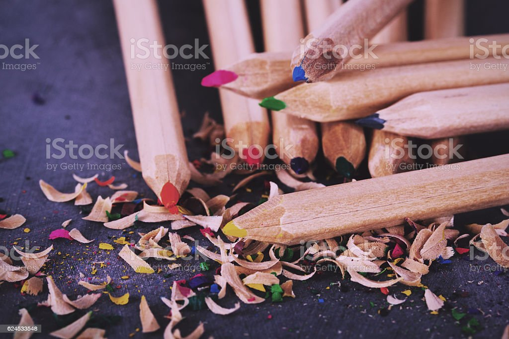Coloured pencils and shavings against a black background Vintage stock photo