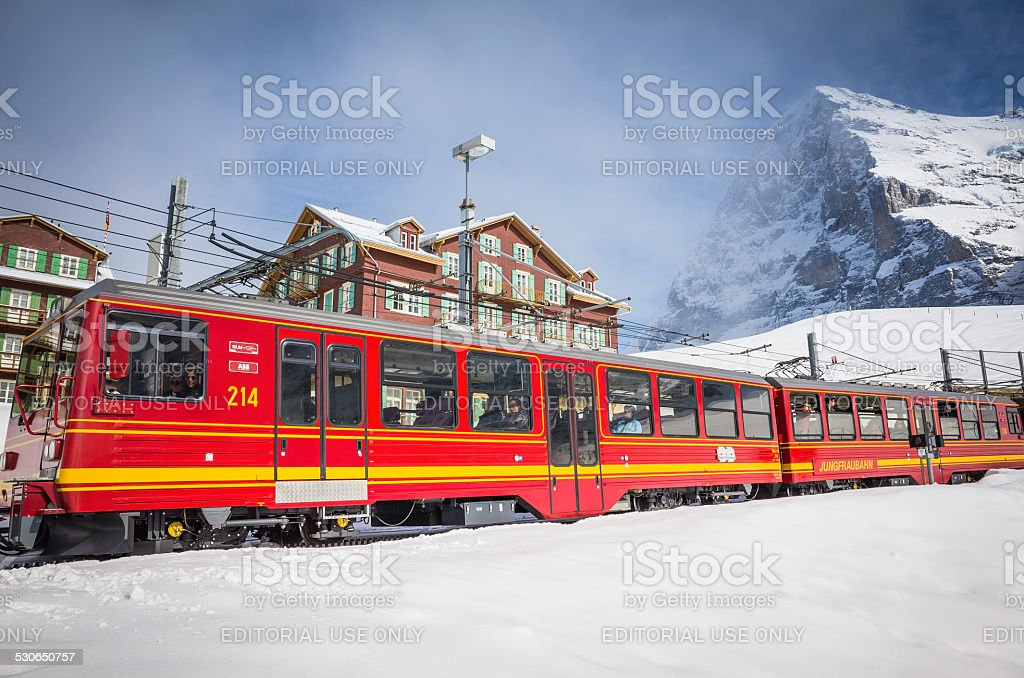 Colourful Alpine railway carrying skiers and tourists snowy resort Switzerland stock photo