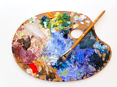 Colourful artists oil paint palette and brush on white
