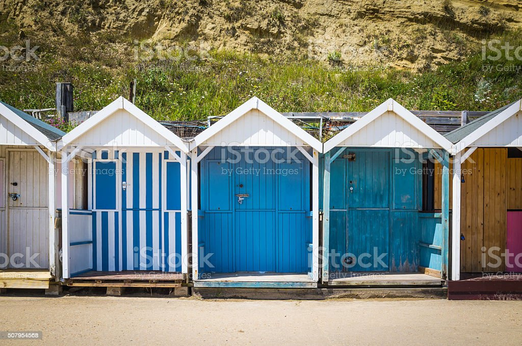 Colourful beach huts on a sunny sandy shore overlooking ocean stock photo