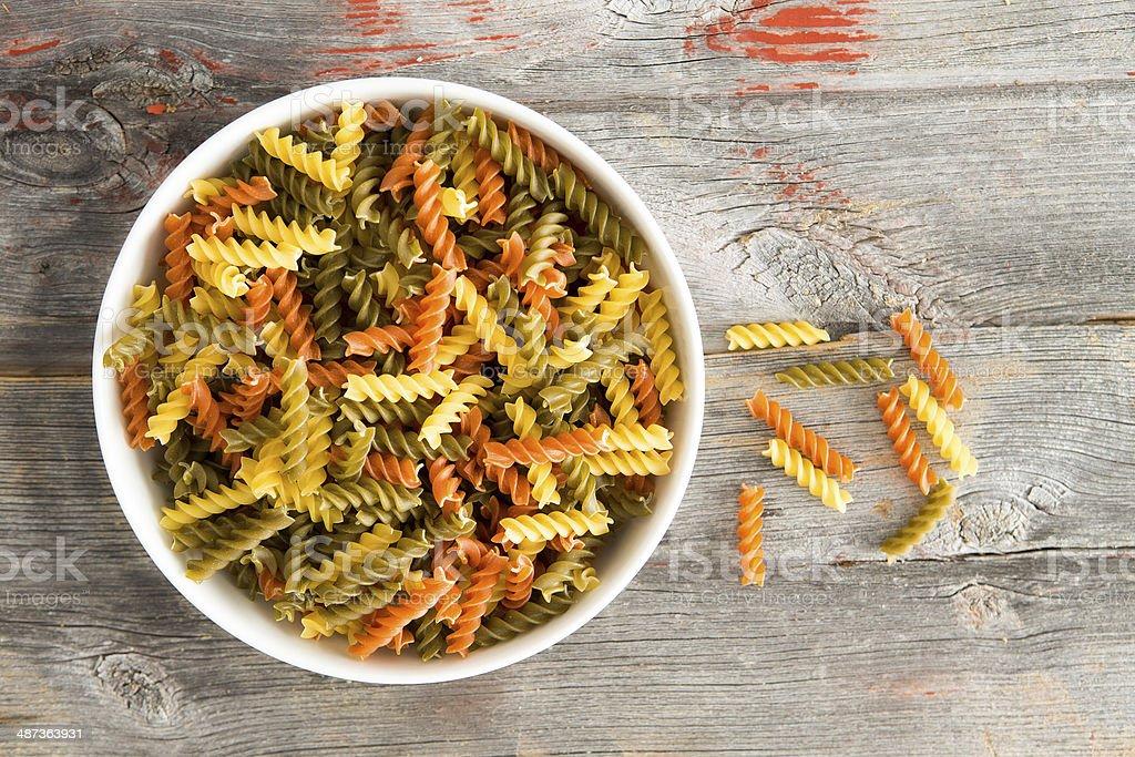 Colourful bowl of tomato and spinach fusilli pasta stock photo