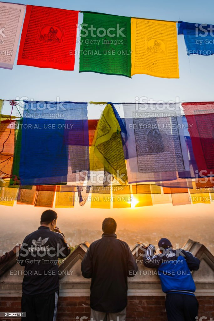 Colourful Buddhist prayer flags local men watching sunrise Kathmandu Nepal stock photo