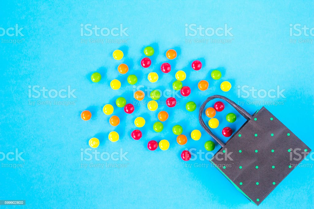 Colourful candy and polka dot paper bag on blue background stock photo
