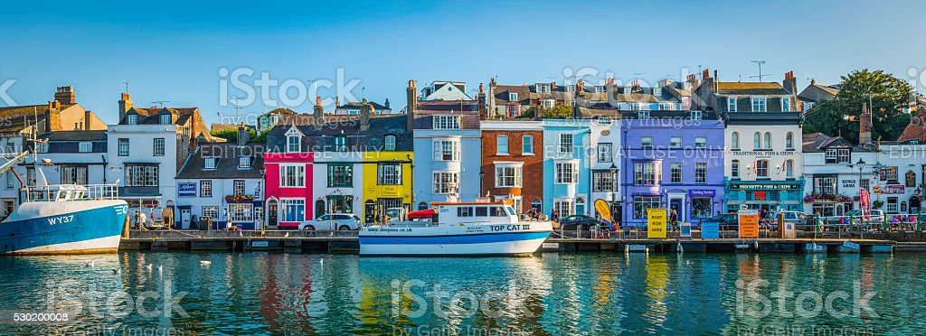 Colourful cottages in idyllic seaside fishing village harbour Dorset UK stock photo