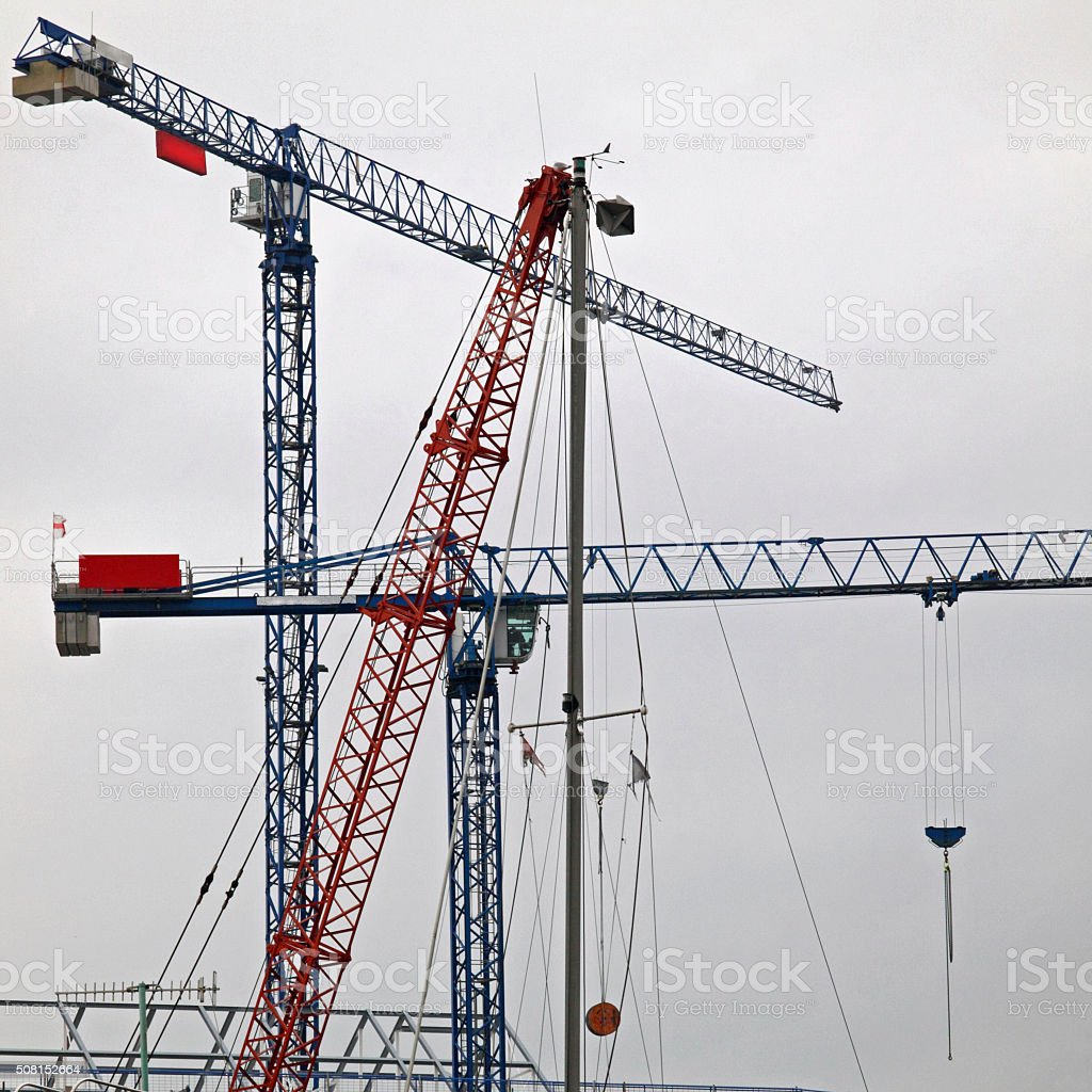 Colourful cranes on a construction site under a grey sky stock photo