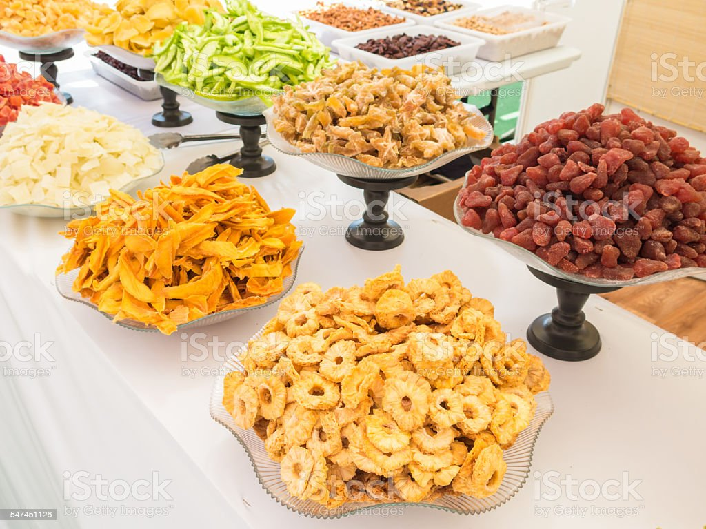 colourful dry fruit for sale in display dishes. stock photo