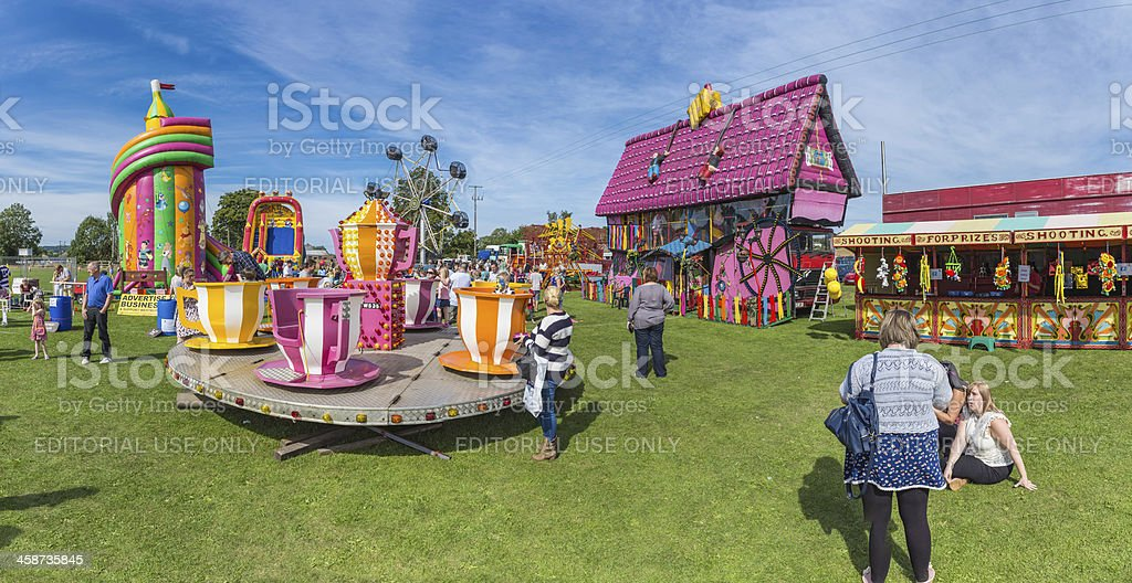 Colourful fairground rides at crowded village summer fair panorama royalty-free stock photo