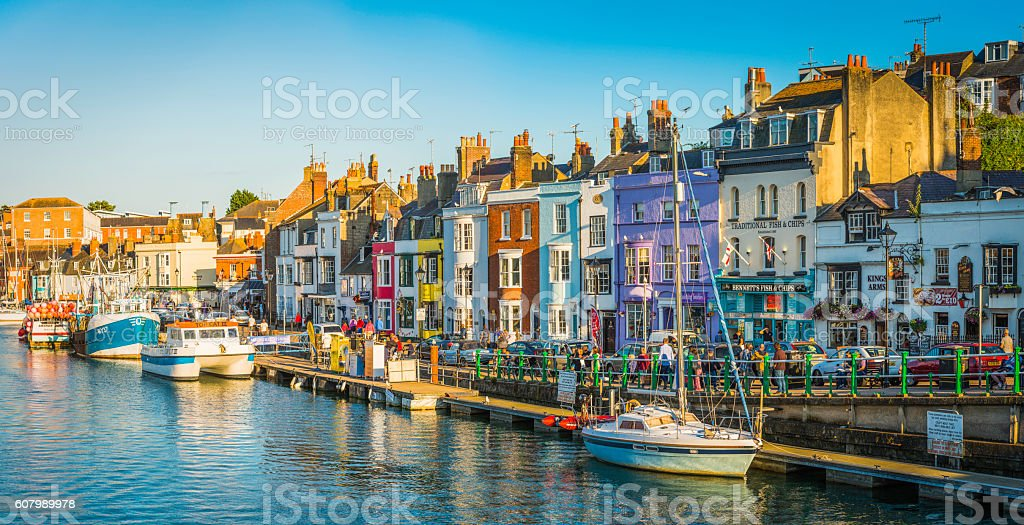 Colourful fishing cottages seaside harbour resort tourists pubs panorama Dorset stock photo