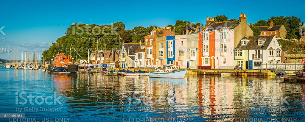 Colourful fishing village homes on tranquil summer harbour Weymouth Dorset stock photo