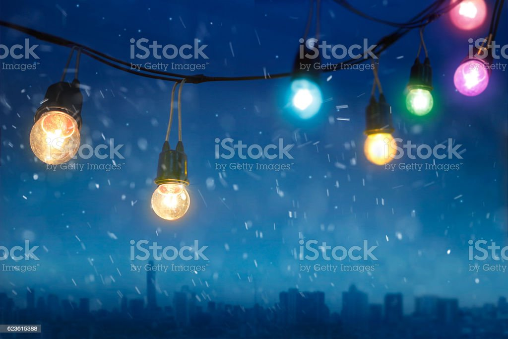 Colourful glowing christmas lights in snowfall on the dark blue stock photo