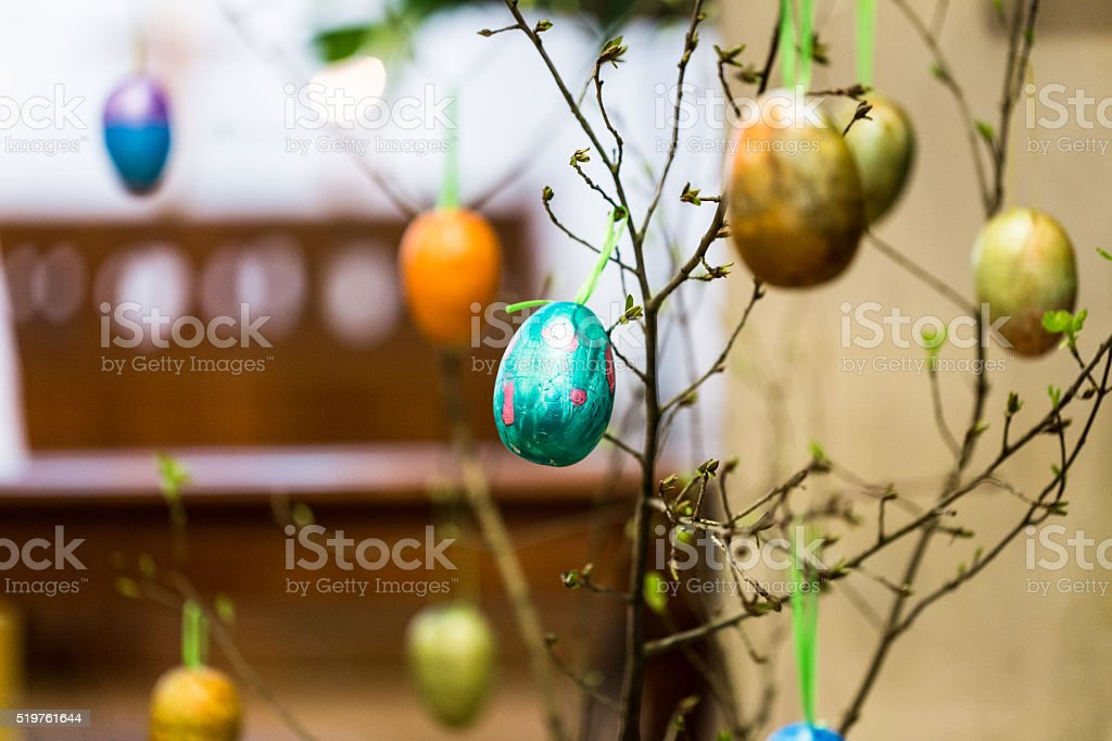 Colourful Hand-Painted Easter Eggs hanging from tree inside Church stock photo