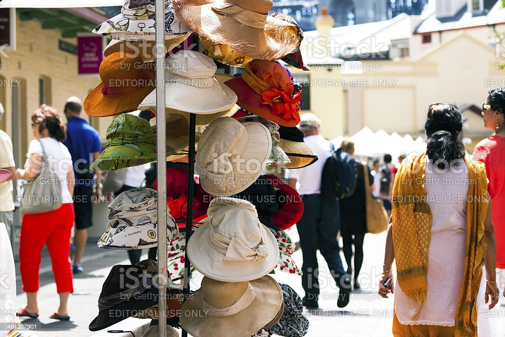 Colourful hats stall with crowd enjoying in sunny day royalty-free stock photo