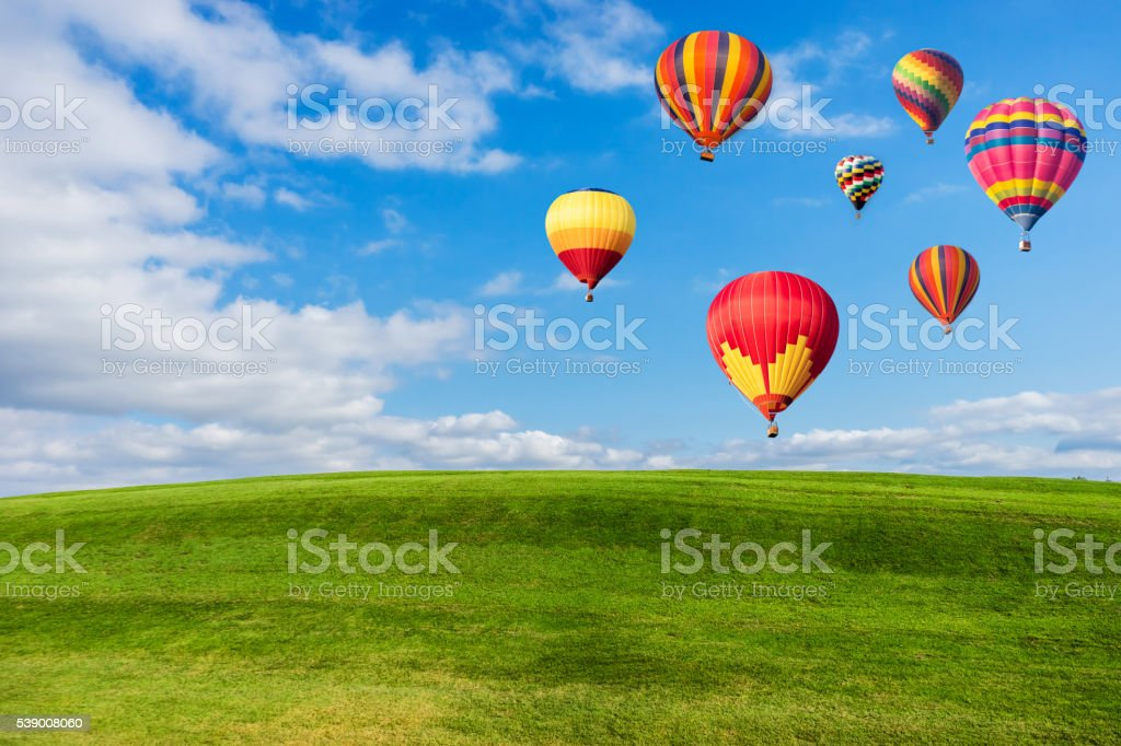 Colourful hot air balloons flying over green field stock photo