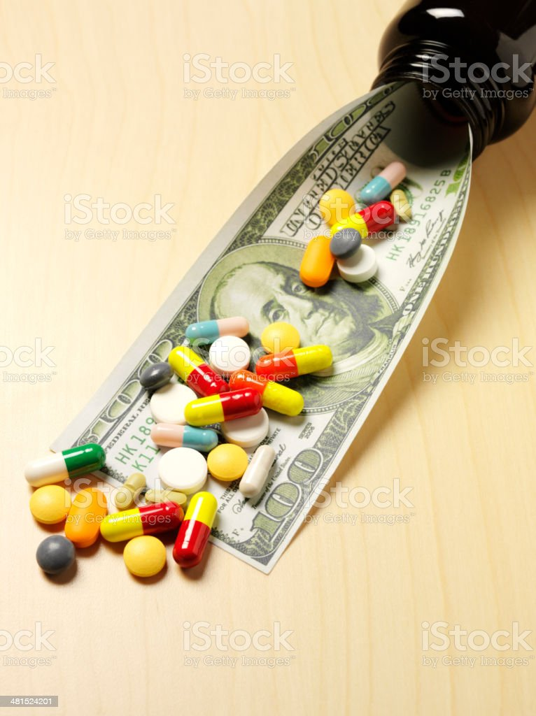 Colourful Medical Tablets on a 100 American Dollar Bill stock photo