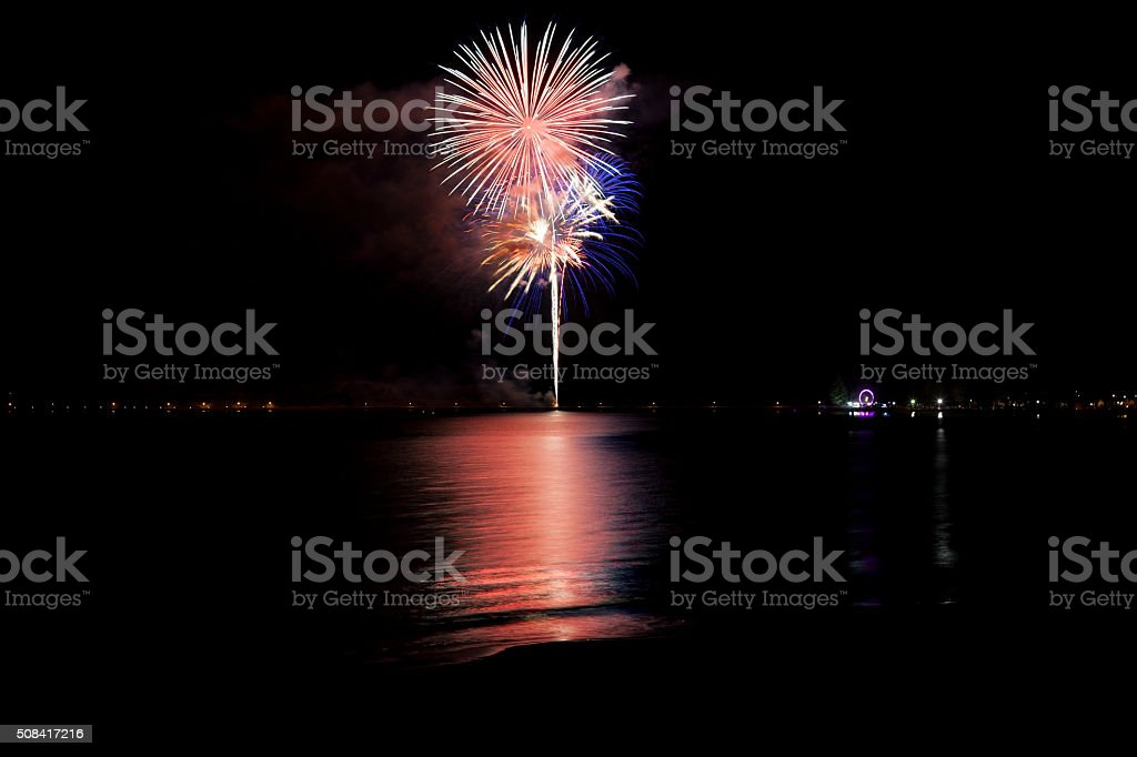 Colourful New Year's Eve fireworks reflected in ocean stock photo