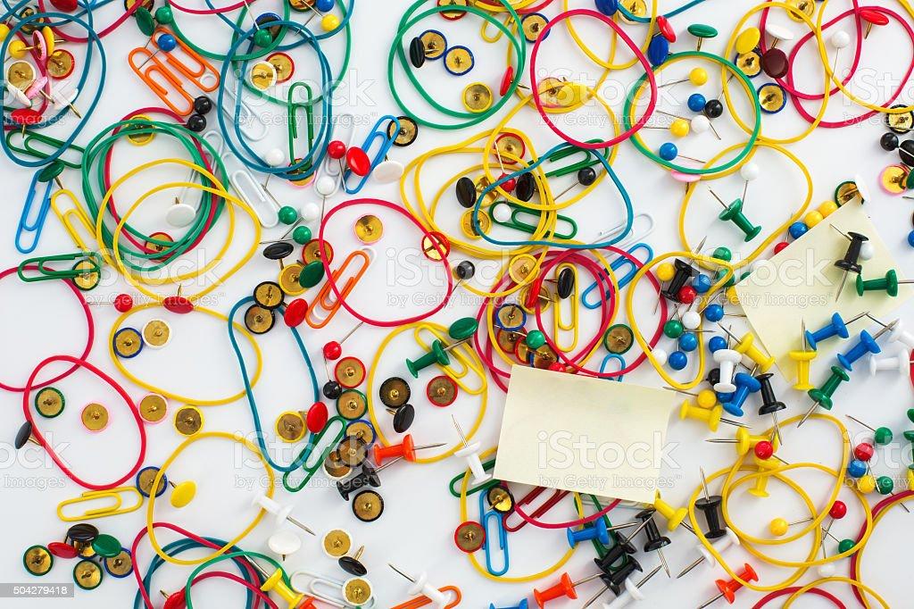 Colourful paper clips, drawing pins thumb tacks, elastic rubber stock photo