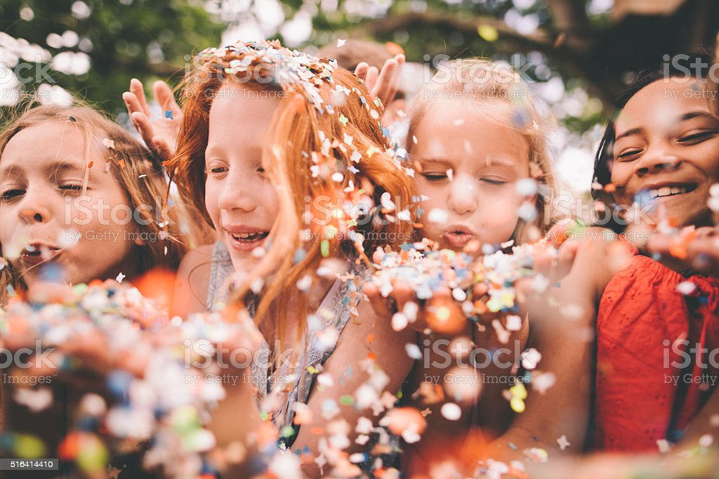 Colourful paper confetti being blown at the camera by children stock photo